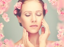 Beauty face of the young beautiful woman with pink flowers in her hair