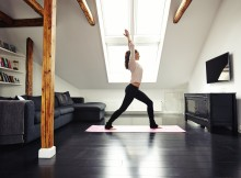 Full length portrait of healthy young lady going yoga workout at home. Fitness model exercising in living room.