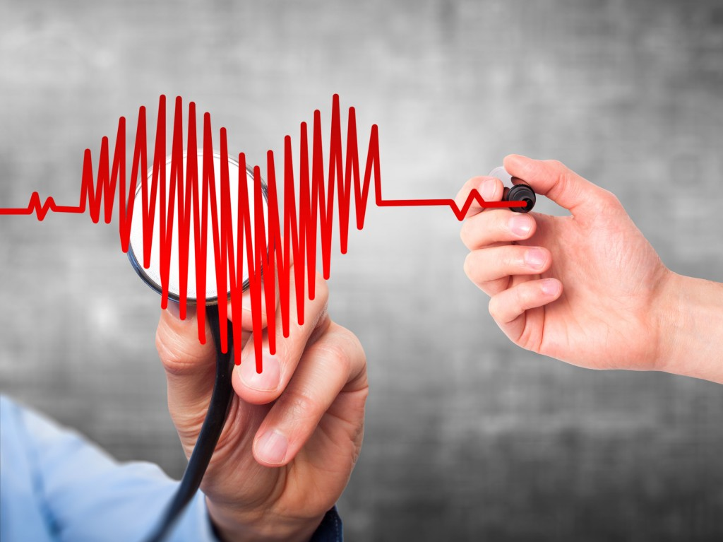 Closeup portrait doctor hand listening to heart beat in heart shape with stethoscope isolated on grey background. Preventive medicine concept