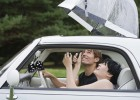 Couple inside car with umbrella out of the sunroof