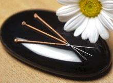 Acupuncture needles on black stone with white daisy