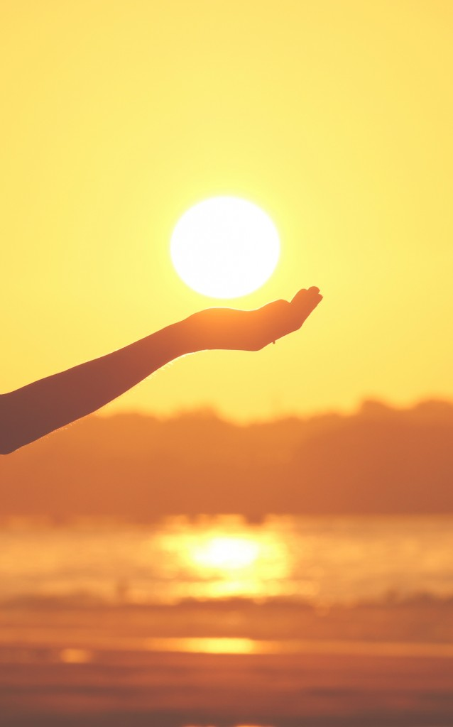 Hand holding the sun at sunset