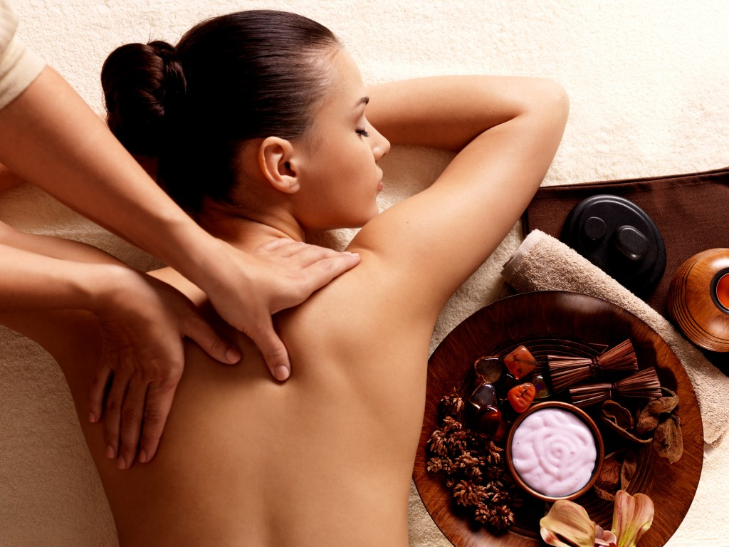 A bowl of spices next to a woman having a back massage