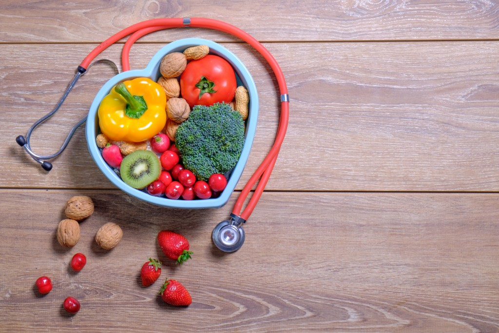 Heart shaped dish with vegetables and stethoscope isolated on wo