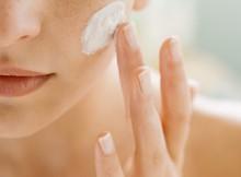 Woman using moisturizing cream on her face