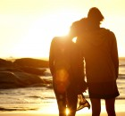 Loving couple holding hands at the beach watching the sunset