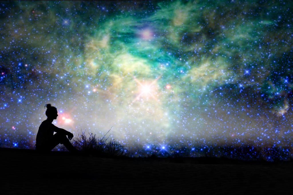 Silhouette of a woman sitting outside, starry night background