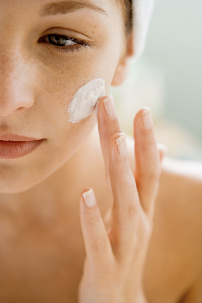 Woman using moisturizing cream on her face